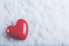Red glossy heart on a frosty white snow background. Love and St. Valentine concept. Stock Image