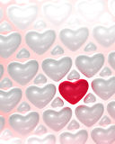 Red glossy heart surrounded by bright hearts Stock Photos