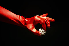 Red Glove holding Pentacle Star. Dramatic red satin glove holds silver pentagram star in a black room Royalty Free Stock Image