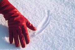 Red glove in the snow. Horizontal top view of woman hand wearing a red leather glove and touching the snow in winter Stock Photography