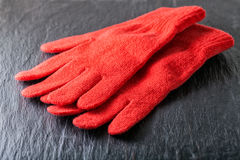 Red gloves on black background. Women`s Red gloves placed on black background Royalty Free Stock Images