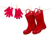 Red Gloves and Red Boots on a line. Red knit glove and red boots pinned to a clothes line. Isolated on a white background stock images