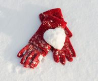 Red gloves and snow heart Stock Photography
