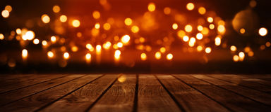 Red glowing bokeh background with wooden table Royalty Free Stock Images