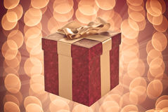 Red glowing gift box. Dark red paper wrapped gift box for Valentine's day on warm illuminated background Royalty Free Stock Photo