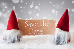 Red Gnomes With Snow, Text Save The Date. English Text Save The Date. Christmas Greeting Card With Two Red Gnomes. Sparkling Bokeh And Noble Silver Background Stock Image