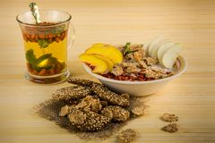 Red goji berries in mint green tea and porridge bowl with oat cookies stock photography