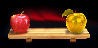 Red and Gold apples. A red and a gold apple placed at opposite ends of a bonded wooden board all isolated upon a black background Stock Image