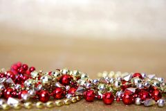 Red and Gold Beaded Necklaces Frame Gold Glitter Background. A collection of red and gold Marti-Gras beaded necklaces frame the bottom of a background of gold Stock Image