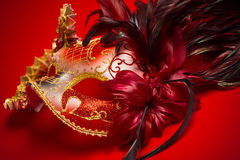 A red, gold and black mardi gras mask on a red background. A red, gold and black mardi gras or venetian mask on a red background