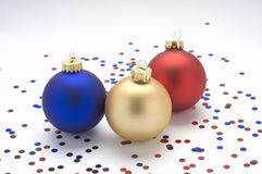 Red,gold,and blue ornaments with confetti. Red,gold,and blue ornaments with confetti Stock Photos