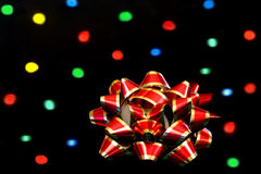 Red and Gold Bow in front of bokeh lights. Royalty Free Stock Images