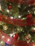 Red and gold Christmas ball decorations. Hanging from a Christmas tree with red ribbon Stock Image