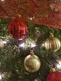 Red and gold Christmas ball decorations. White and gold Christmas ball decorations hanging on a Christmas tree with some red ribbon Royalty Free Stock Photos