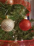 Red and gold Christmas ball decorations. Gold and white Christmas ball decorations hanging on a Christmas tree with some red ribbon stock image