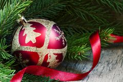Red and gold Christmas ball, fir branches and red tape, selective focus royalty free stock photo
