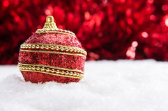 Red and gold Christmas ball in snow with tinsel, christmas background Stock Images
