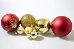Red and gold christmas balls decorations in a white background royalty free stock image