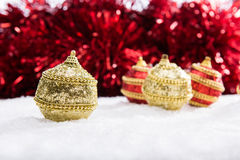 Red and gold Christmas balls in snow with tinsel, christmas background Royalty Free Stock Photo