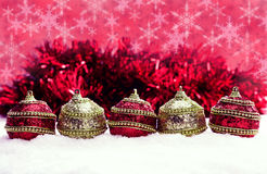 Red and gold Christmas balls in snow with tinsel and snowflakes, christmas background Royalty Free Stock Image