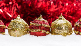 Red and gold Christmas balls in snow with tinsel and snowflakes, christmas background Royalty Free Stock Images