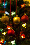 Red and gold christmas bauble and a tree in the ba Royalty Free Stock Images
