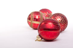 Red and Gold Christmas Baubles. Four red christmas baubles with gold trim set against a white background Royalty Free Stock Photo