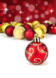 Red and gold Christmas baubles. With stars and out of focus baubles in the background Stock Image