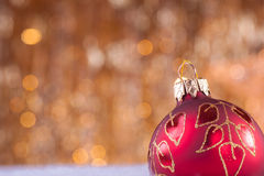 Red and gold christmas baubles. On background of defocused golden lights Stock Photo