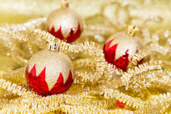 Red and gold Christmas. Baubles on background of defocused golden lights Royalty Free Stock Photo
