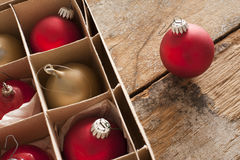Red and gold Christmas baubles in a box. Red and gold Christmas baubles in a brown cardboard box with a single red ball outside on a rustic wooden table with Royalty Free Stock Images