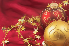 Red and gold christmas bulbs on a red background Stock Photos