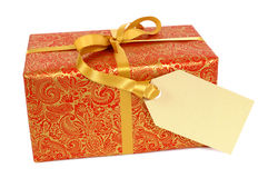 Red and gold Christmas gift with gift tag label isolated on white background Royalty Free Stock Photography
