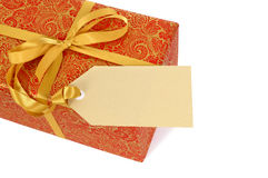 Red and gold christmas gift with ribbon and gift tag label isolated on white background Royalty Free Stock Photos