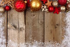 Red and gold Christmas ornament border with snow on wood Royalty Free Stock Photography
