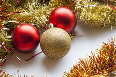 Red and gold decorative Christmas ball and garland on white background Stock Photos