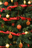 Red and Gold Decotrations on Christmas Tree. Gold and Red Decorations on a Christmas Tree with shiny red ribbons Stock Image