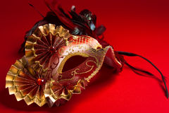 A red and gold feathered Venetian mask on red background Royalty Free Stock Photo