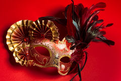 A red and gold feathered Venetian mask on red background Stock Photo