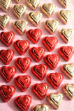 Red and gold foil wrapped heart shape chocolate pieces Stock Images