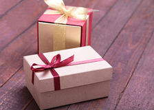 Red and gold gift box on wood background. Stock Photography
