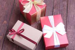 Red and gold gift box on wood background. Royalty Free Stock Images