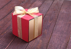 Red and gold gift box on wood background. Royalty Free Stock Photography