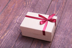 Red and gold gift box on wood background. Stock Photo