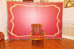 Red and gold improvised Studio in the Baroque style in front of classic festive interior. chair to sit. Area for the photo shoot, the background for the Royalty Free Stock Photo
