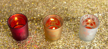 Red, gold and silver candlesticks. On the gold background Royalty Free Stock Photo