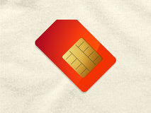 Red and gold telephone sim card on crumpled material Stock Image