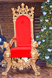 Red-and-gold throne of Santa Claus. Stand near the fireplace and is decorated with a toy Christmas tree Stock Image
