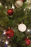 Red and gold and white Christmas ball decorations. White and gold and white Christmas ball decorations hanging on a Christmas tree with some red ribbon stock photos