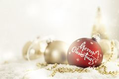 Red and golden balls for Christmas. Red and golden colored Christmas balls with greeting in artificial snow Stock Photography